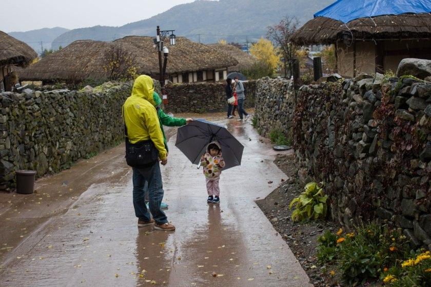 Un niño sostiene un paraguas desproporcionado. Dentro de unos años se pasará a un móvil de las mismas características.